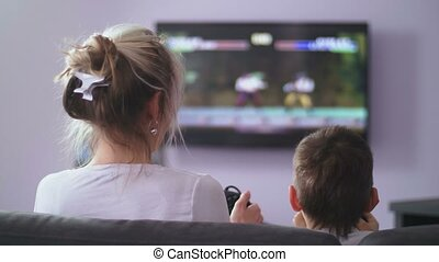 Back view mom with son playing shooter video game - Rear...