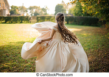 Back view of a beautiful bride spinning in a wedding dress dancing on the green field