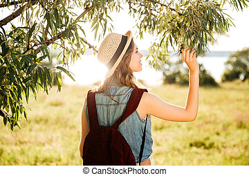 Back view of a beautiful girl traveling in the forest