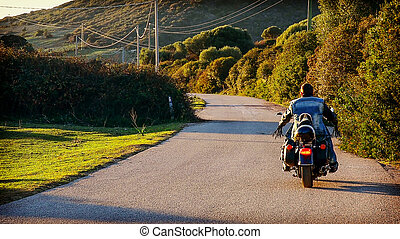 Back view of a biker on a classic motorcycle