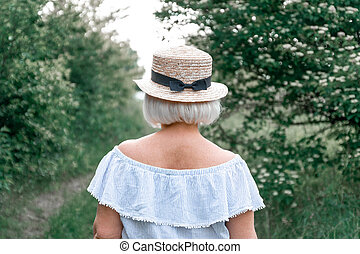 Back view of a blonde girl in straw hat with a bow in the summer garden