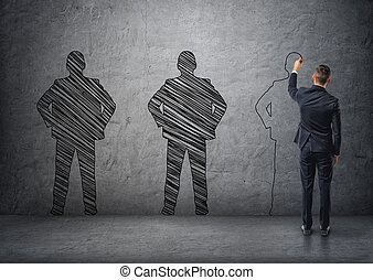 Back view of a businessman drawing dark men's silhouettes on concrete wall