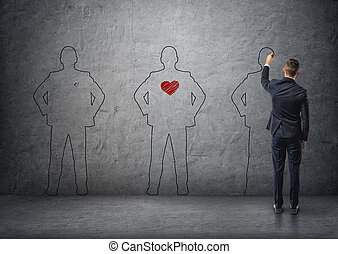 Back view of a businessman drawing men's silhouettes on concrete wall. The middle one with red heart in its chest.