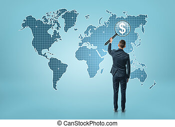 Back view of a businessman looking at world map through magnifying glass and seeing dollar sigh