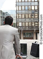 Back view of a businessman standing outside with computer and briefcase