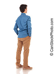 back view of a casual man with hands in pockets - back view...