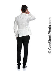 back view of a confused business man scratching his head