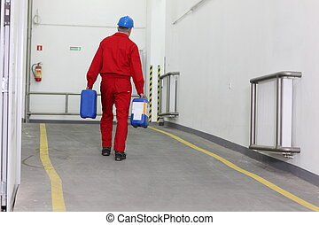 Back view of a factory worker carrying bottles of chemicals