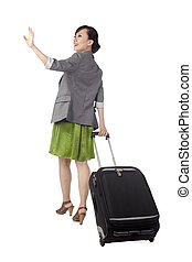 back view of a female traveler gesturing goodbye