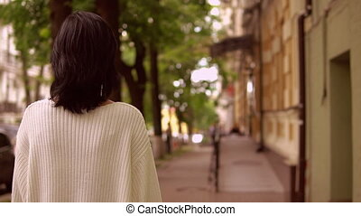 back view of a female walking along the street in a city