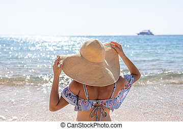 Back view of a girl in a big hat on the seashore.