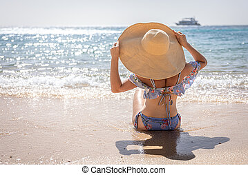 Back view of a girl in a big hat sits on the seashore.