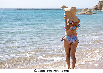Back view of a girl in a swimsuit and a hat on the beach.
