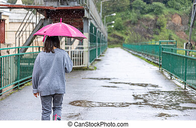 Back view of a girl under an umbrella on a walk in the rain.
