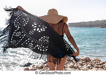 Back view of a girl with a cape on the seashore.