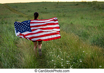 Back view of a girl with an American flag in a field among the grass.