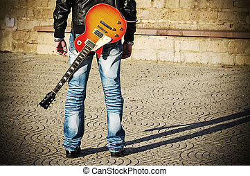back view of a guitarist standing with a guitar