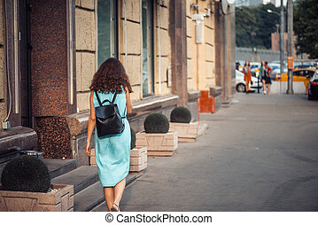 Back view of a hipster girl in a blue dress with black leather backpack walking on city street