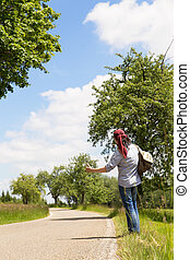 back view of a hitchhiking man on a road