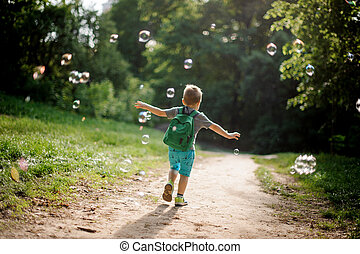 Back view of a little boy playing with soap bubbles in summer park on sunny day