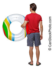 Back view of a man in shorts with an inflatable circle.