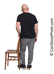 back view of a man standing with a chair in white background