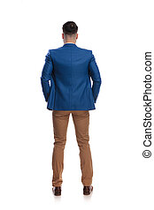 back view of a man standing with hands in pockets