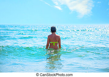 Back view of a pretty young woman on the sea