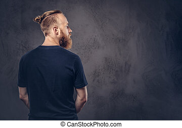 Back view of a redhead bearded man dressed in a black t-shirt. Isolated on the dark textured background.