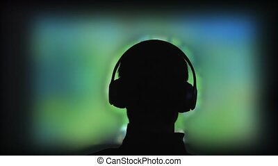 Back view of a silhouette of a young man plays video games...