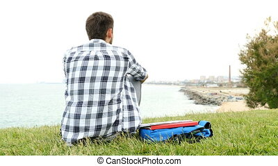 Back view of a student sitting on the grass contemplating the city