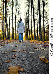 Back view of a teenager girl walking in a road limited by trees at sunset