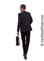 walking business man holding a briefcase - back view of a...