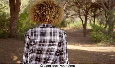 Back View Of A Walking Woman On The Forest Road.