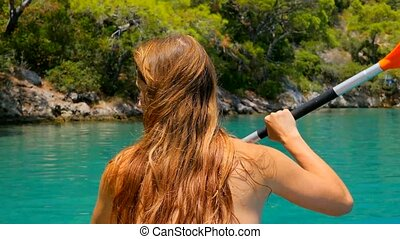 Back view of a woman kayaking in the sea.