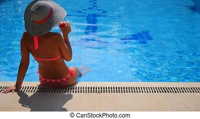 Back view of a woman relaxing in swimming pool.