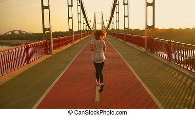 back view of a woman running along the bridge