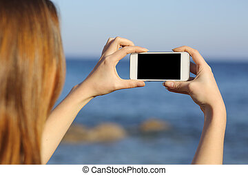 Back view of a woman taking photograph with a smart phone camera at the horizon on the beach