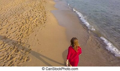 Back view of a woman walking barefoot along wet sand beach. Running wave is washing away footprints on the sand