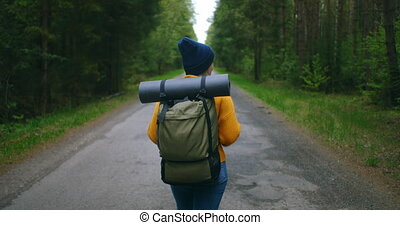 Back view of a woman with a backpack in a yellow sweater and hat walking along a road in the woods in slow motion.