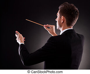 Back view of a young composer directing with his baton