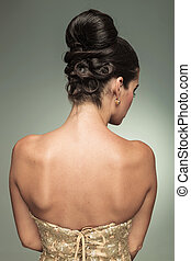 back view of a young elegant woman with nice hairstyle, in studio