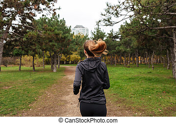 Back view of a young fitness woman