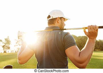 Back view of a young man carrying golf club