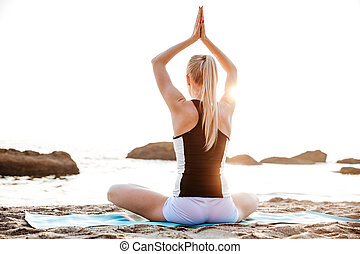 Back view of a young woman sitting and meditating outdoors