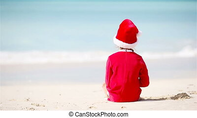 Back view of adorable girl in Christmas hat on white beach...