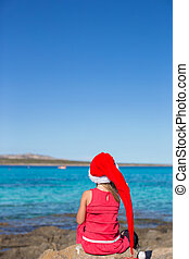 Back view of adorable little girl in Santa hat on big stone...