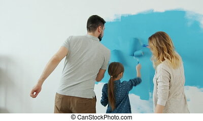 Back view of adorable young family mum dad and daughter painting wall in apartment