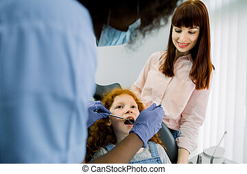 Back view of African female pediatric dental specialist making oral checkup of little curly red haired school girl, visiting dentist with her young mom. Dentist office, pediatric dentistry