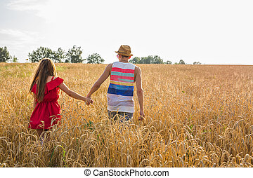 Back view of amorous couple walking in the field